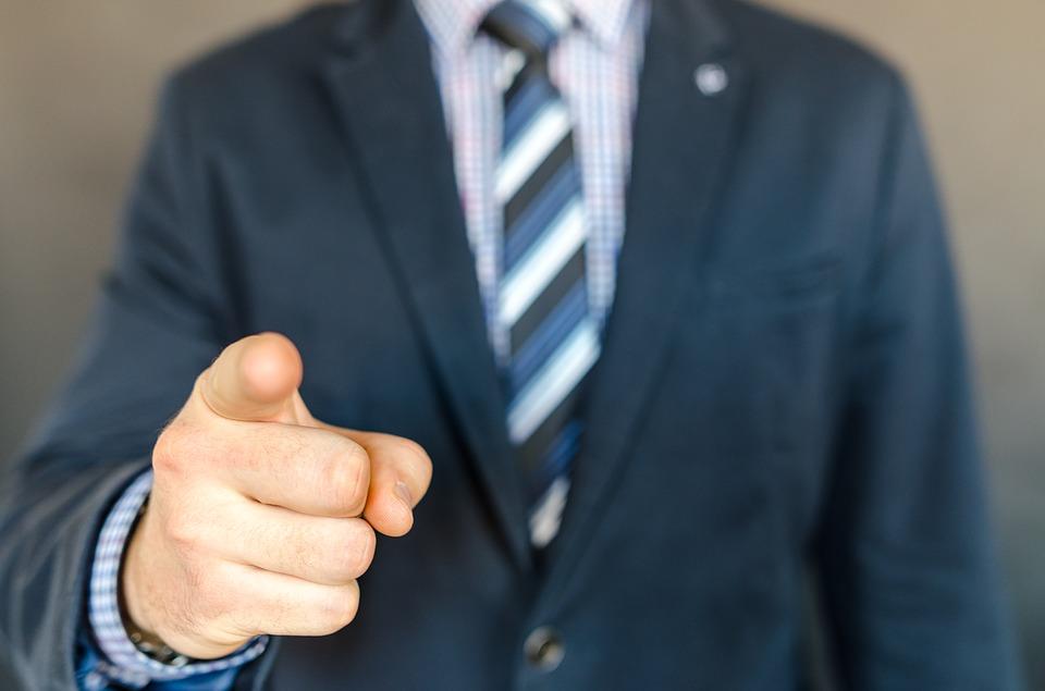 指を指すスーツの男